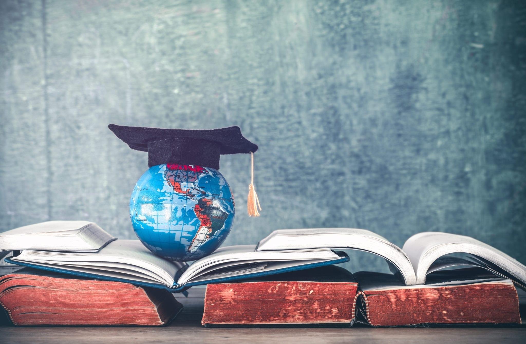 """< img src=""""Najlepsze-uczelnie-na-świecie.jpg"""" alt=""""Graduation cap with Earth globe model map on book stack. education concept."""">"""